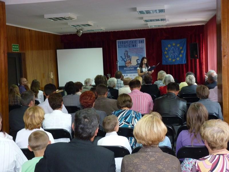 Wprowadzenie do obchodów przez dyrektora biblioteki Dorotę Karkusiewicz. Widok na salę pełną publiczności.